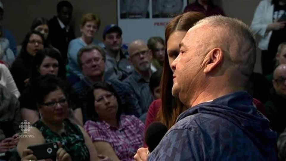 Un homme s'adresse à une foule.