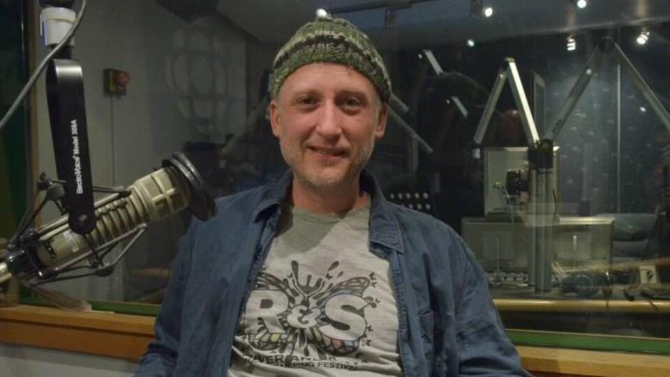 Peter Zwarich au micro de CBC Sudbury, avec une tuque et une chemise bleue en jeans ouverte sur un chandail gris.