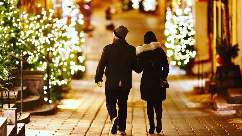 Un couple déambule dans le Petit Champlain à l'aube de Noël, à Québec.