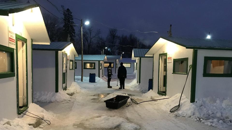 Deux personnes debout devant des cabanes blanches installées sur la glace.