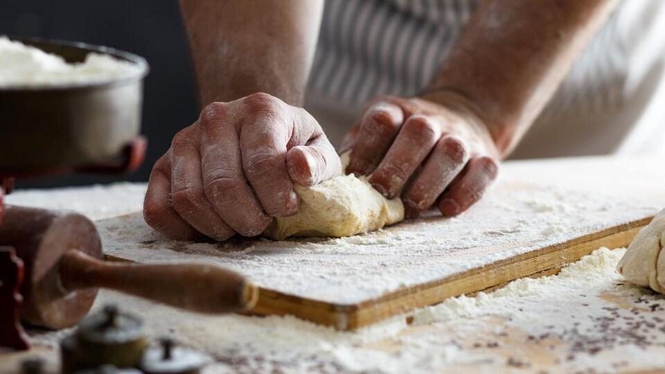 Un homme pétrit de la pâte à pain sur un plan de travail enfariné.