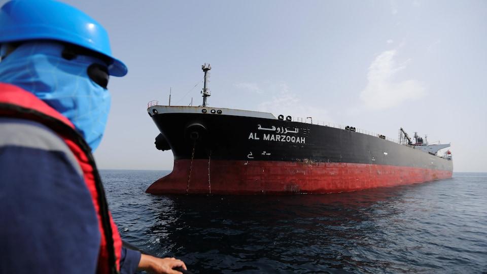 Un homme masqué regarde le pétrolier saoudien.