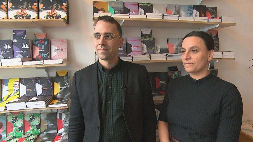 Un homme avec des lunettes et une femme sourient. Derrière eux, des livres de la maison d'édition.