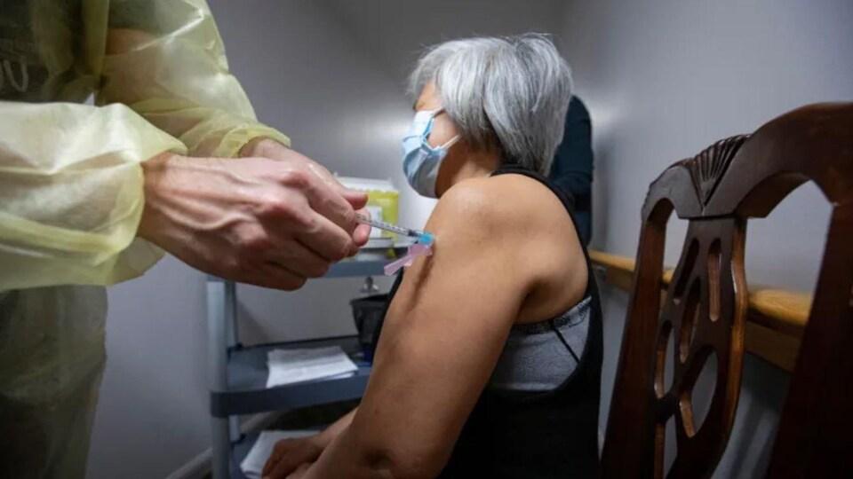Une personne âgée reçoit sa première dose du vaccin.