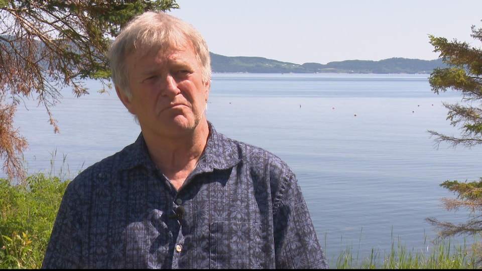 Jean-Marie Fallu lors d'une entrevue devant une baie, en été.