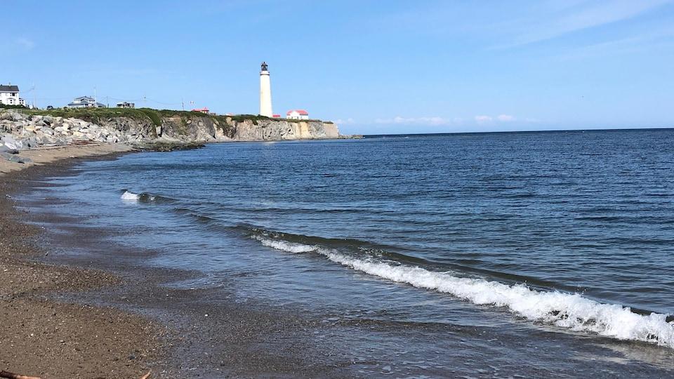 Le phare juché sur un cap, avec en avant-plan une grève et le Saint-Laurent.