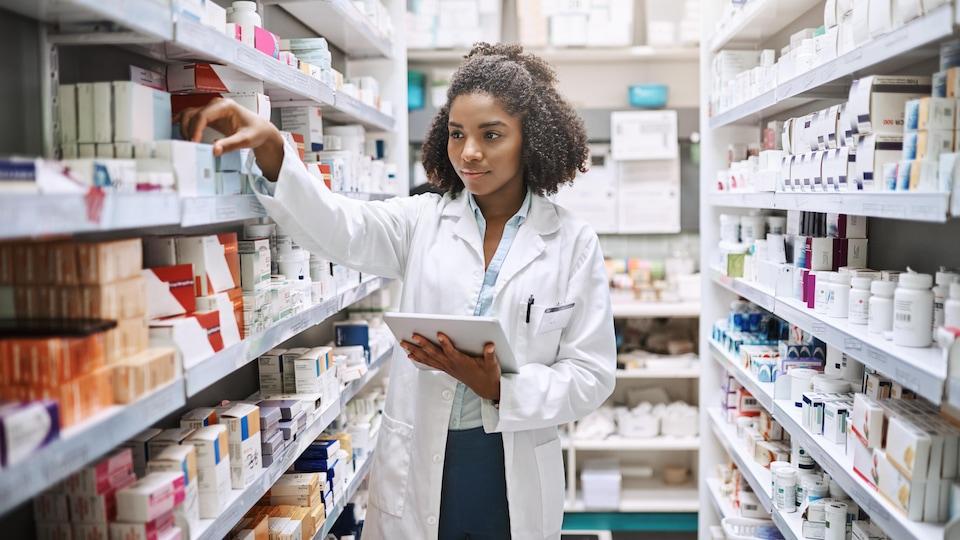 Une jeune femme sélectionne des médicaments dans une pharmacie.
