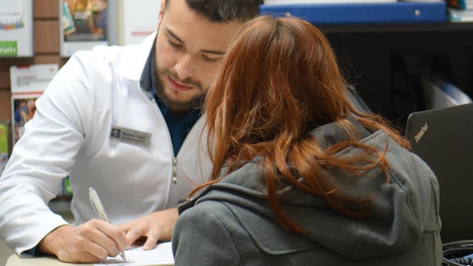 Un pharmacien assis derrière une table prend des notes en discutant avec une cliente.