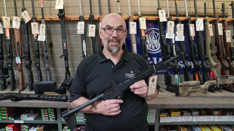Un homme tient une arme dans une boutique.