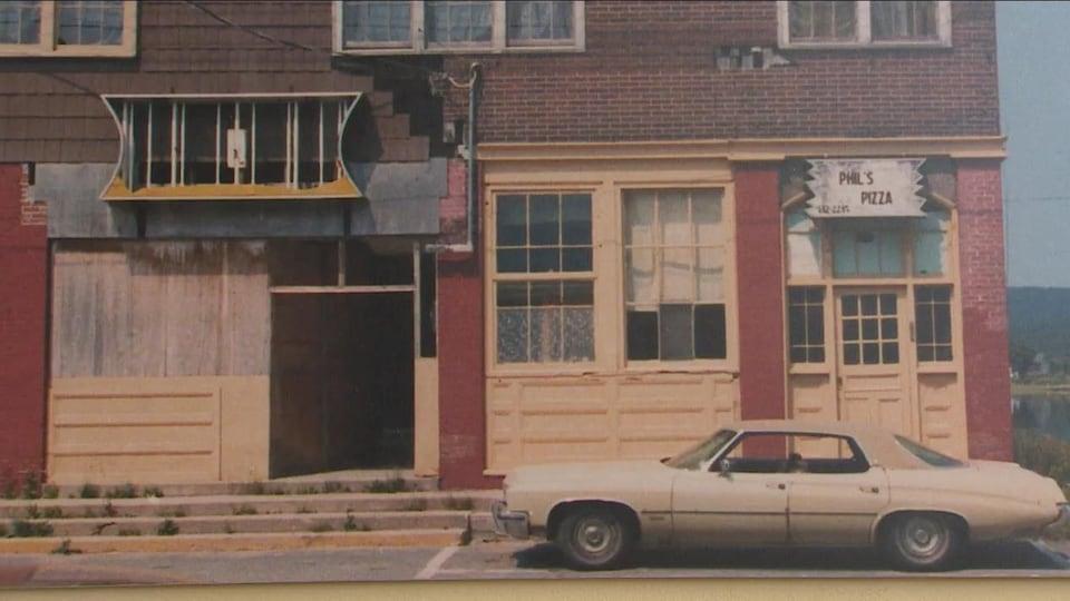 Une photo des années 1970 où l'on voit un vieux théâtre en ruine et une voiture devant celle-ci. Un écriteau minuscule : Phil's Pizza.