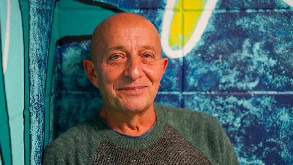 Portrait en couleur de l'auteur et illustrateur jeunesse Philippe Béha, souriant, avec en arrière plan un mur peint en bleu et jaune