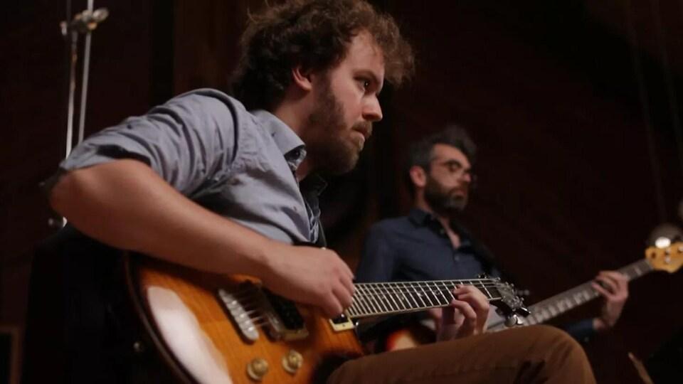 Philippe Bouchard joue de la guitare.