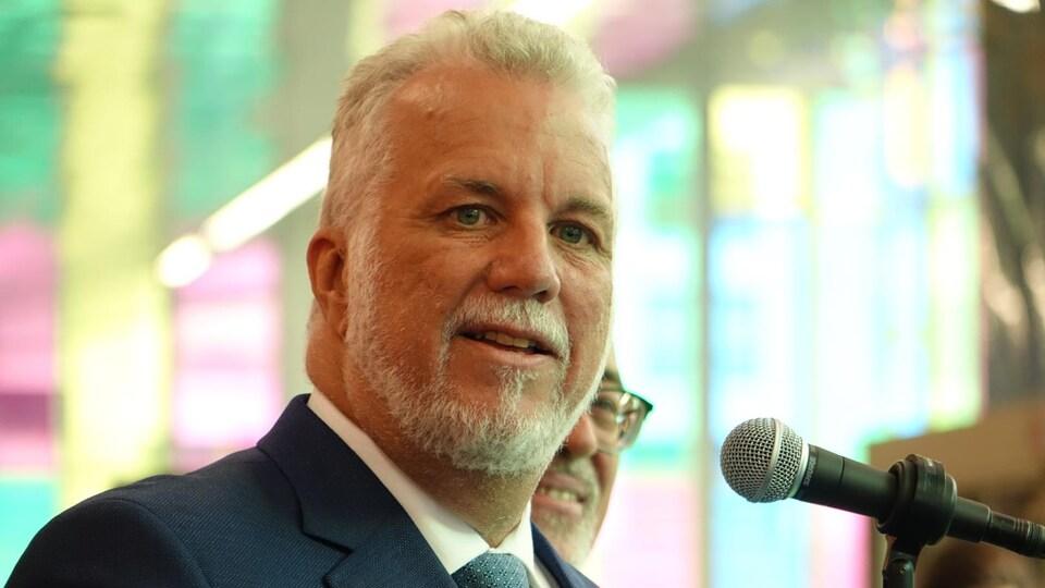 Philippe Couillard parle dans un micro dans la verrière du Palais des congrès.