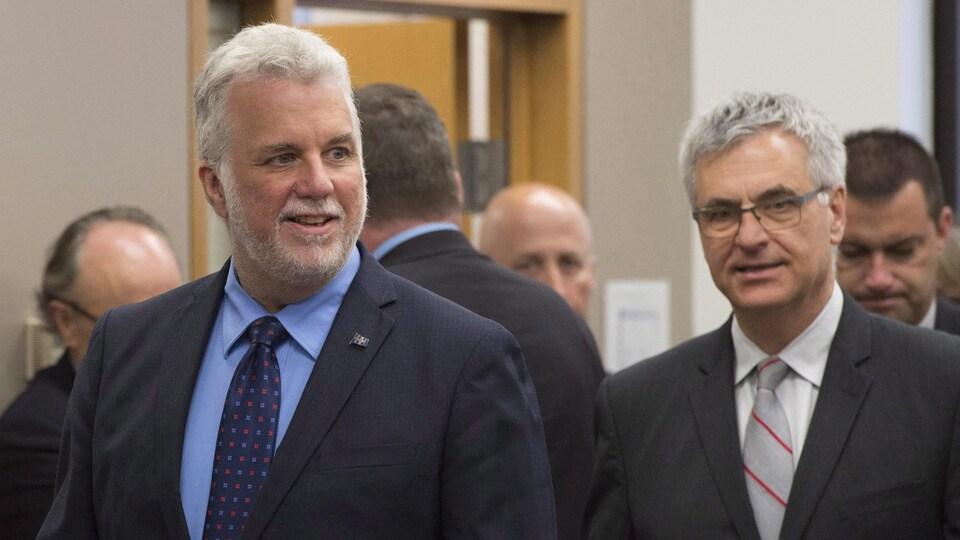 Deux hommes vêtus d'un veston et d'une cravate marchent dans un couloir.