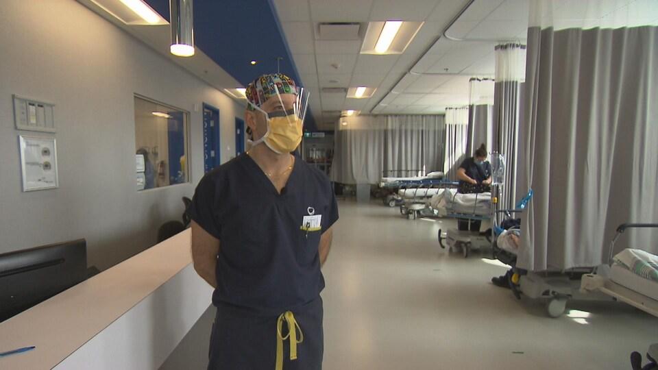On voit le Dr Dahan, debout, en habit de travail et portant la visière et le masque chirurgical. Derrière lui, les lits d'hôpital.