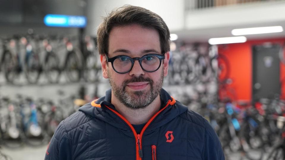 Un homme portant des lunettes noires et un manteau sport devant une rangée de vélos