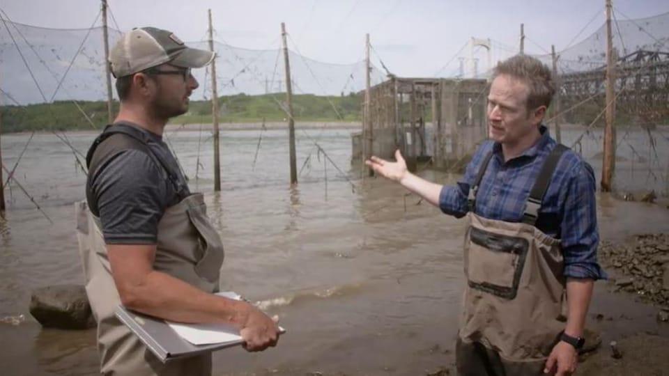 Deux hommes discutent au bord du fleuve Saint-Laurent. De grandes clôtures immergées se situent derrière eux dans le fleuve.