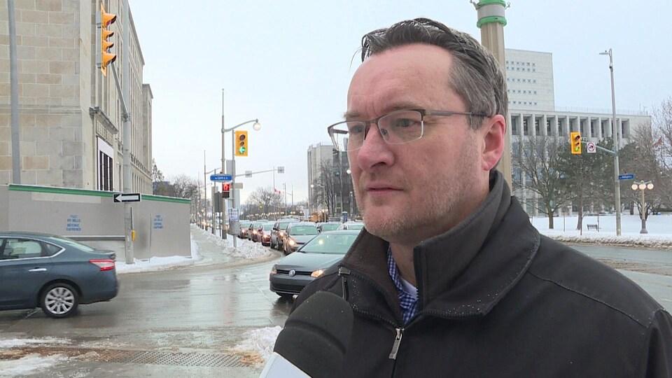 Philippe Landry est en entrevue à Radio-Canada sur la rue Wellington au centre-ville d'Ottawa.
