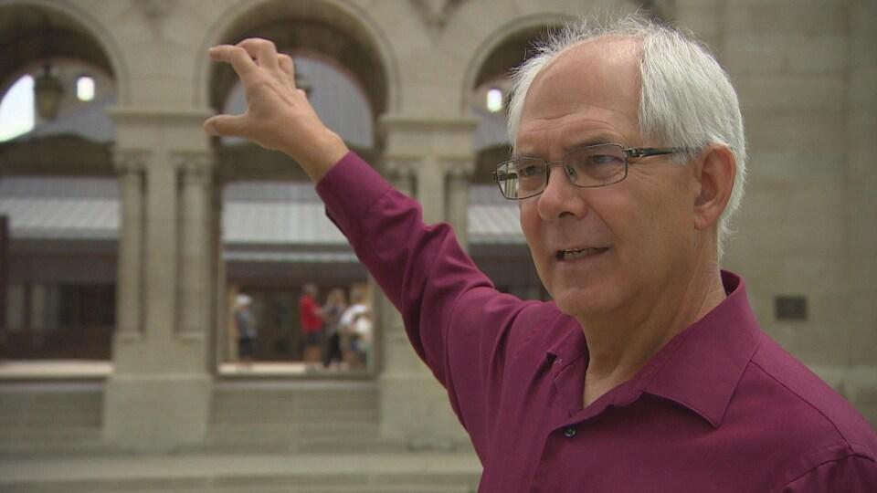 Un homme à lunettes et en chemise couleur bordeaux lève le bras devant la cathédrale de Saint-Boniface.