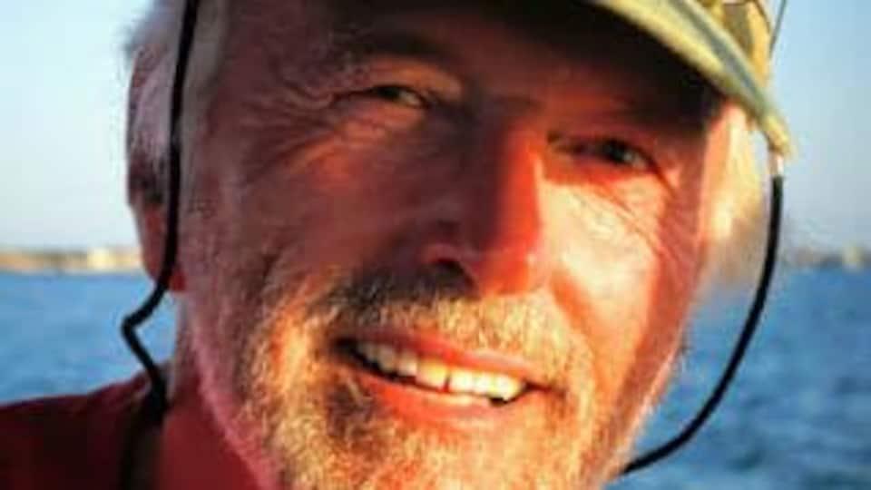 Un homme portant la barbe et une casquette sourit à bord d'un voilier.
