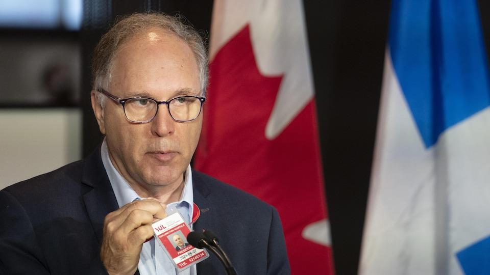 Philippe Rainville debout derrière un micro durant une conférence de presse.
