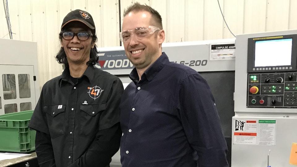 Glen Generoso, un travailleur philippin devant équipement de Set 47, à Valcourt. À ses côtés, le copropriétaire de l'atelier d'usinage Philippe Morin.