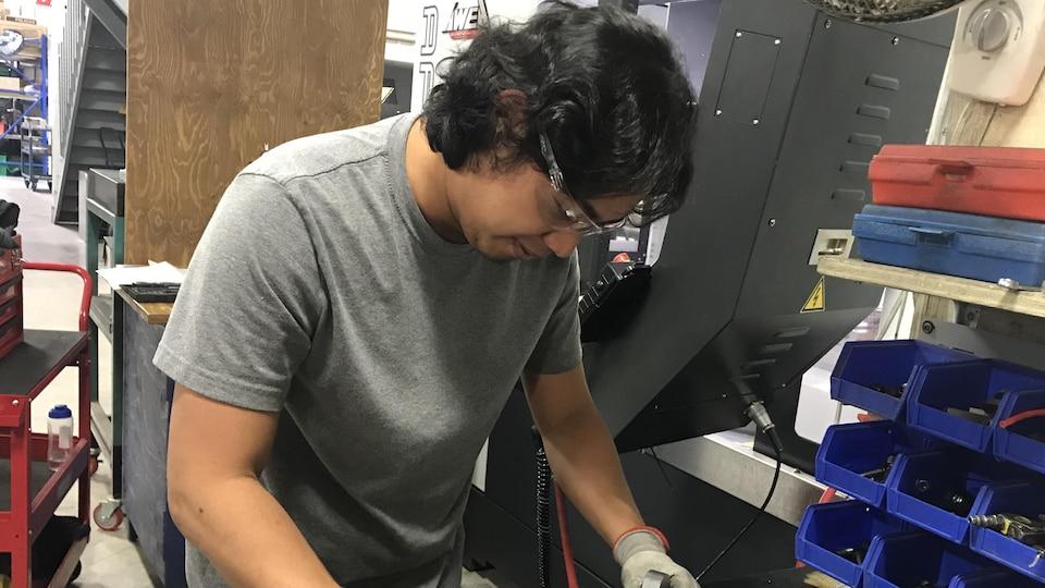 Ezekiel Tare, un des Philippins embauchés chez Usinage Lemay à Bonsecours se penche sur une pièce à son poste de travail.
