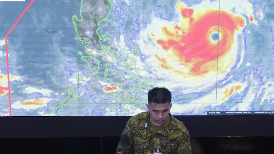Un membre de l'armée de l'air philippine se tient devant une image satellite du typhon Mangkhut, le 13 septembre 2018.
