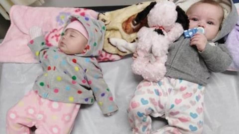 Deux bébés couchés côte à côte. L'un dort, l'autre regarde quelque chose.