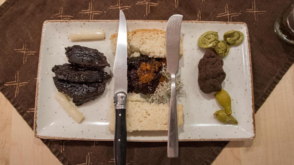 Un plat, deux couteaux et trois morceaux de viande