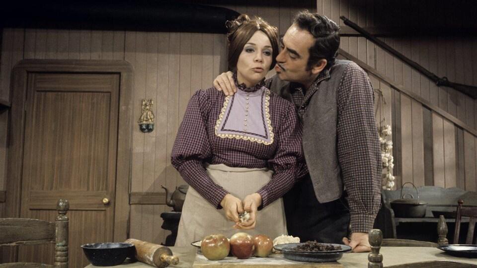 Un couple de la fin du 19e siècle est debout dans une cuisine. L'homme s'apprête à embrasser sa femme pendant qu'elle pèle des pommes.