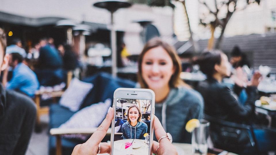 Une jeune femme se fait photographier à l'aide d'un cellulaire.