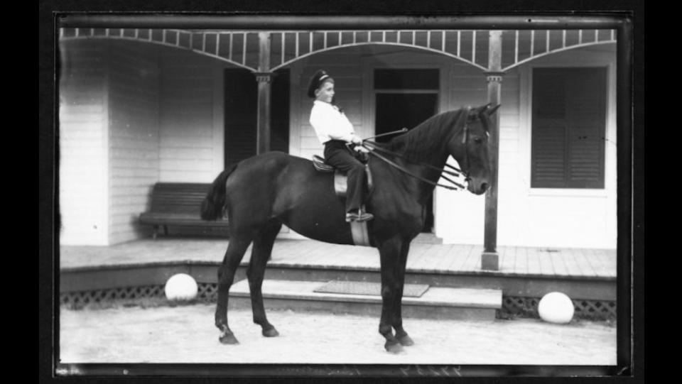 Vue du jeune Paul Livernois sur son cheval, devant la résidence d'été de Jules-Ernest Livernois à Petite-Rivière
