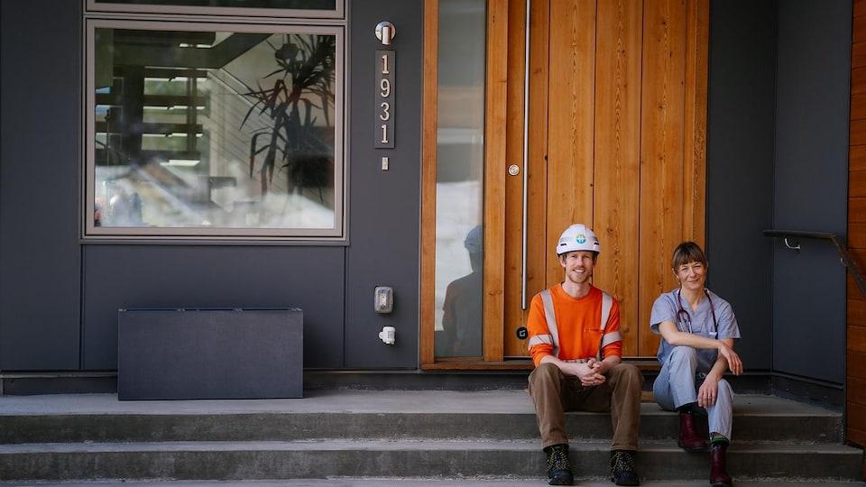 Un travailleur de la construction et une travailleuse de la santé posent sur leur perron durant le confinement qu'impose la pandémie de la COVID-19.