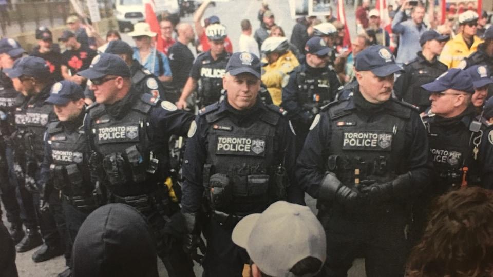 Plusieurs policiers de Toronto lors d'un contrôle de foule. Au moins l'un d'entre eux porte des gants renforcés.