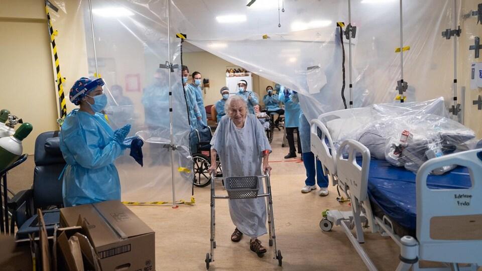 Une dame officiellement guérie de la COVID-19, tenant une marchette et habillée d'une robe d'hôpital, avance sous les applaudissements du personnel de la santé. Elle est souriante.