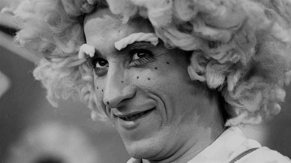 Le comédien porte une perruque et du maquillage.