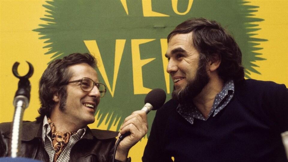 Pierre Paquette tend un micro à Claude Jasmin, qui sourit.