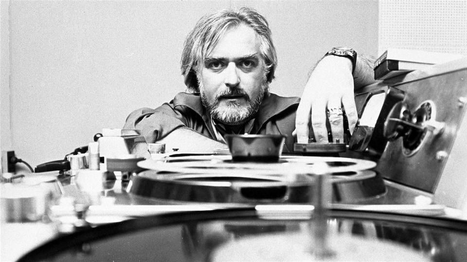L'animateur Jacques Languirand devant un magnétophone en 1971. Sa main touche un ruban et il regarde la caméra directement.