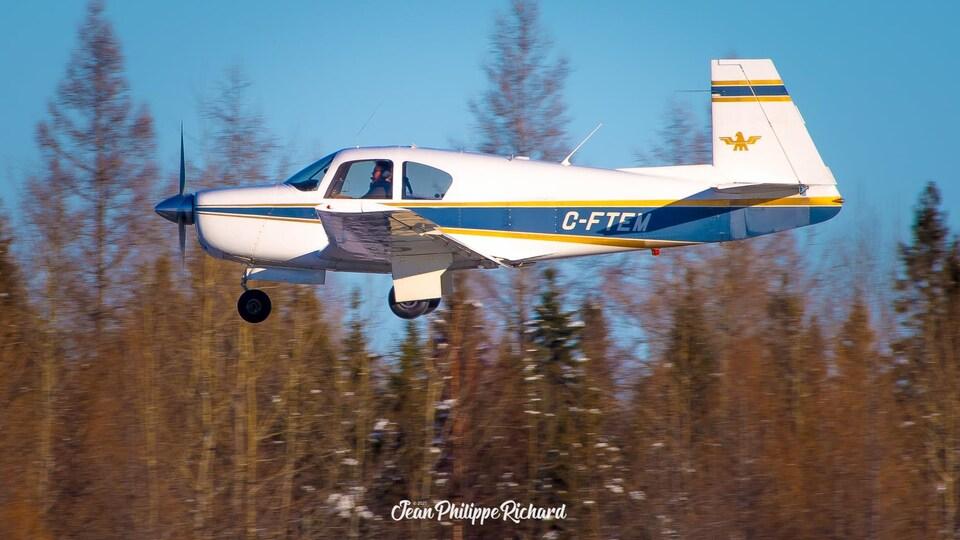 Un petit avion C-FTEM avec une hélice en avant survole à la hauteur de la cime des arbres.