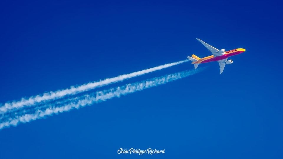 Un avion jaune et mauve dans le ciel bleu clair laisse une traînée de fumée blanche derrière lui.