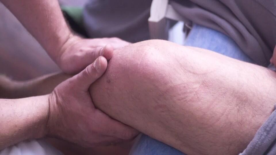 Un physiothérapeute masse la jambe de quelqu'un.