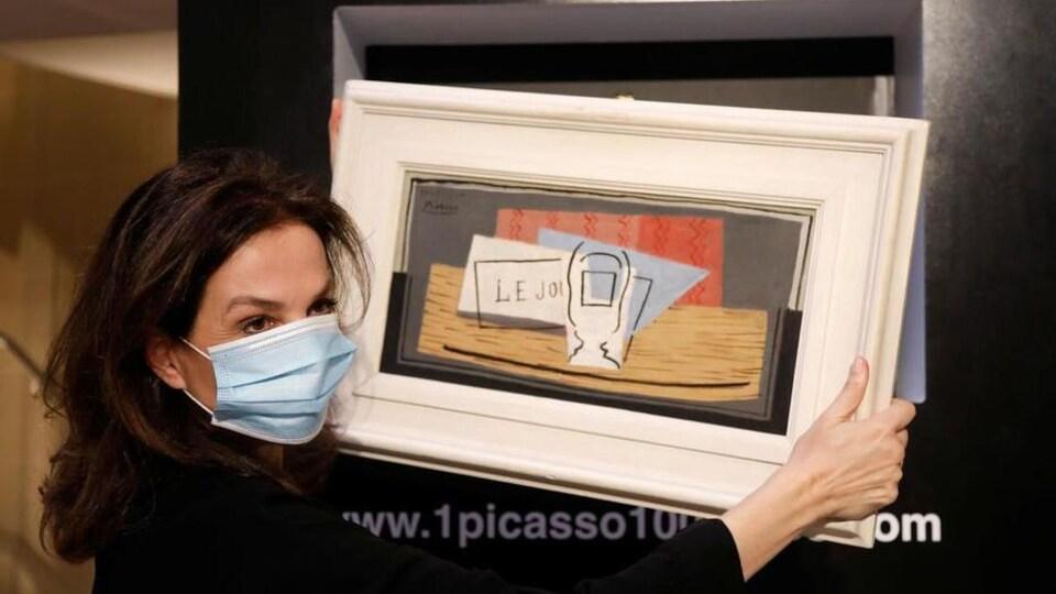 Une femme portant un masque hygiénique tient la toile de Picasso entre ses mains.