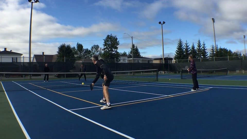 Quatre personnes jouent au pickleball sur un terrain de tennis.