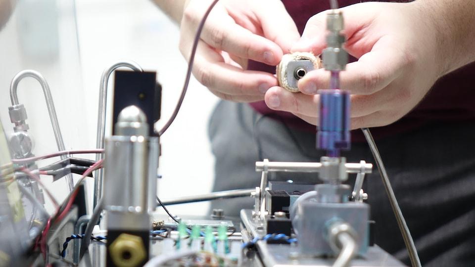 Un homme tient un échantillon dans salive dans un tube, face au prototype de la firme Picomole.