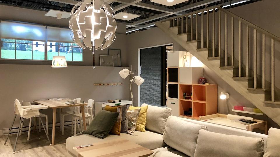 Pièce en démonstration du nouveau magasin IKEA de Québec. On aperçoit un sofa, une table de cuisine avec deux chaises, des espaces de rangement et un escalier.