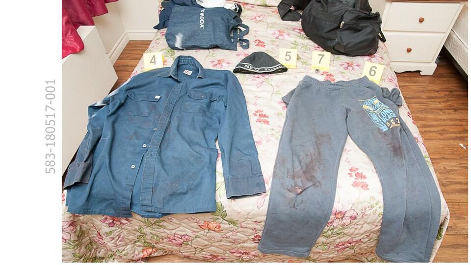 Des vêtements ensanglantés sur un lit pour identification judiciaire