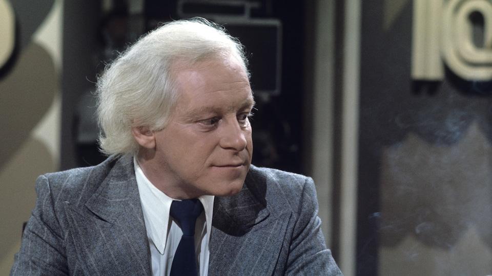 Dans un studio de télévision, Un Pierre Bourgault songeur est assis. Il y a de la fumée dans l'air.