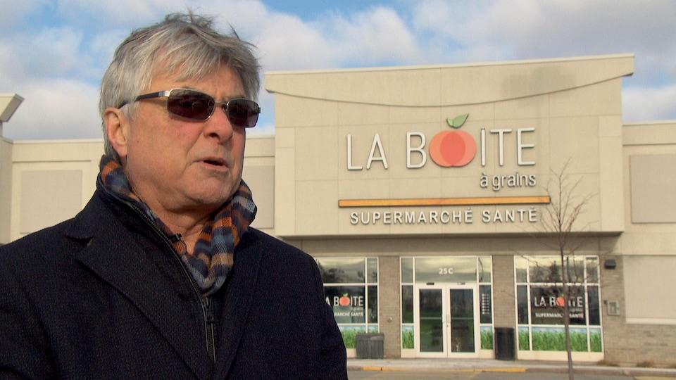 Pierre Daniel Ménard en entrevue à l'extérieur devant l'un de ses commerces.