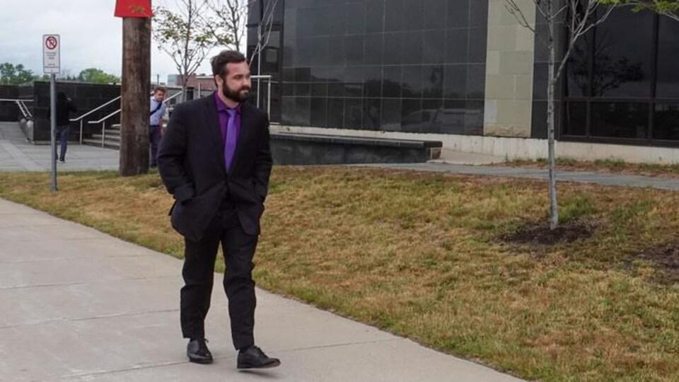 Un homme en complet cravate qui marche devant le palais de justice à Moncton.